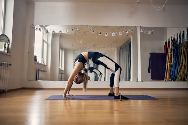 Young slim woman in sportswear exercising in the gym alone while stretching, doing bridge pose