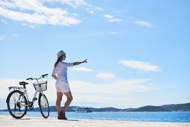 Молодая стройная женщина, стоя на велосипеде на каменистом тротуаре под голубым небом