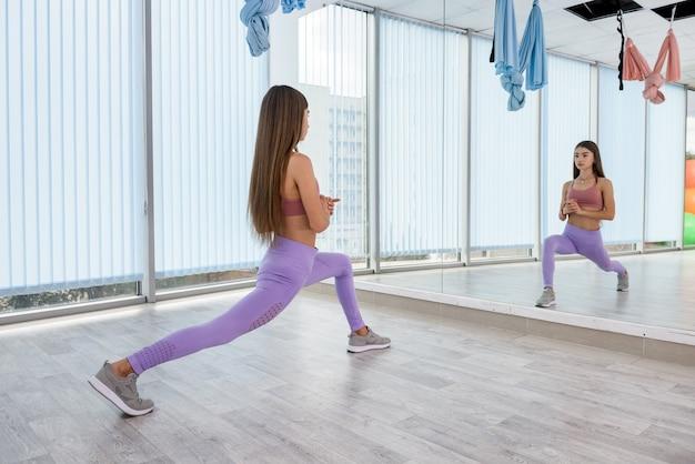 健康的なライフスタイルのための筋肉の機能トレーニングをストレッチする若いスリムな女性。美しい女性の体はハードワークアウトをアフレット