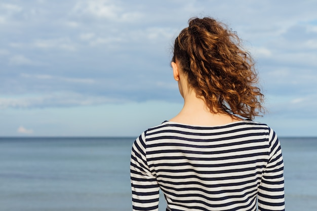 Young slim woman in striped t-shirt and with curly hair looking at the sea