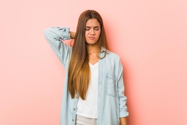 Молодая стройная женщина страдает от боли в шее из-за малоподвижного образа жизни.