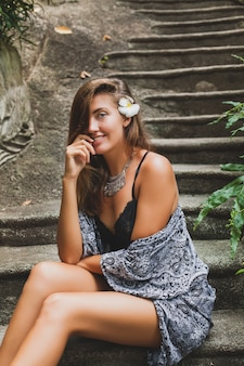 Giovane donna sottile nella villa tropicale di bali, indossa lingerie sexy, sensuale, bella, civettuola, pelle abbronzata, abbigliamento alla moda, stile etnico boho, camicia da notte, mantello, bellezza naturale