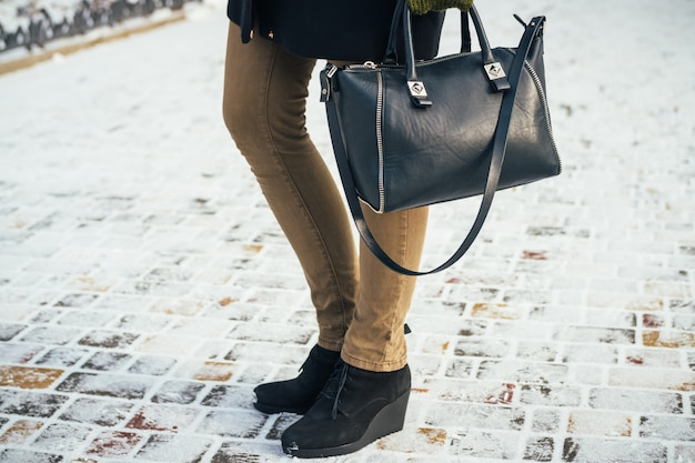 Young slim woman walking in the park with the purse in the winter