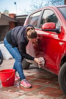 Молодая стройная женщина моет дверь красной машины с ковриком