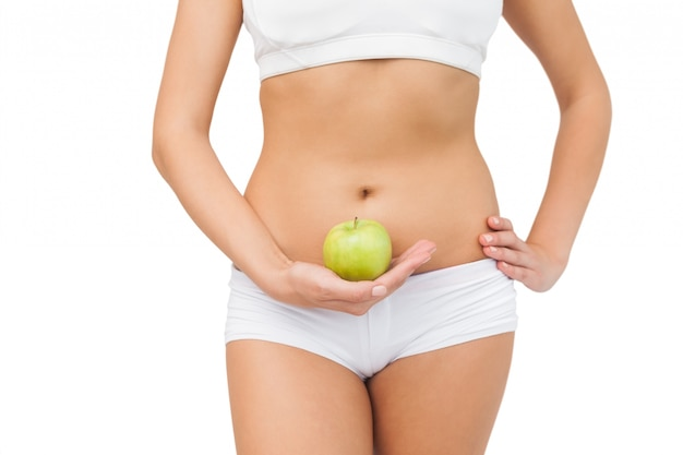 Young slim woman wearing a sports bra holding a green apple