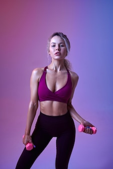 Young slim woman with dumbbells poses in studio, neon background. sportswoman at the photo shoot, sport concept, active lifestyle motivation