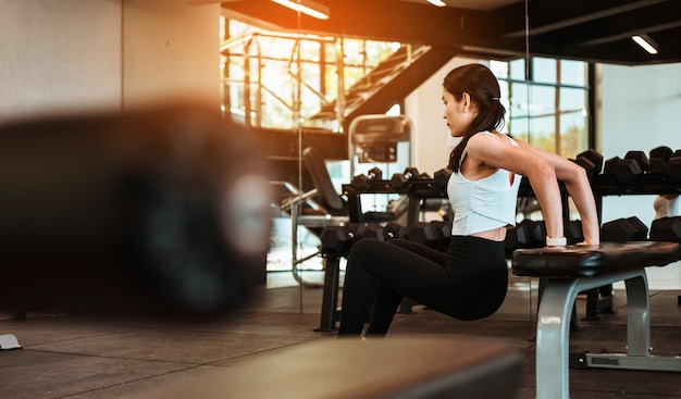 Young slim woman working out on exercise chair in fitness gym