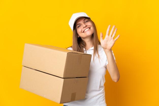 Молодая женщина-словацкая курьерская женщина изолирована на желтом фоне, считая пять пальцами