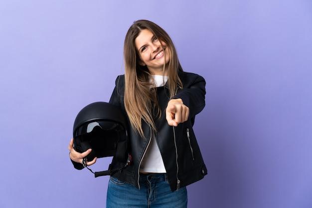 幸せな表情で正面を指し紫の背景に分離されたオートバイのヘルメットを保持している若いスロバキア女性