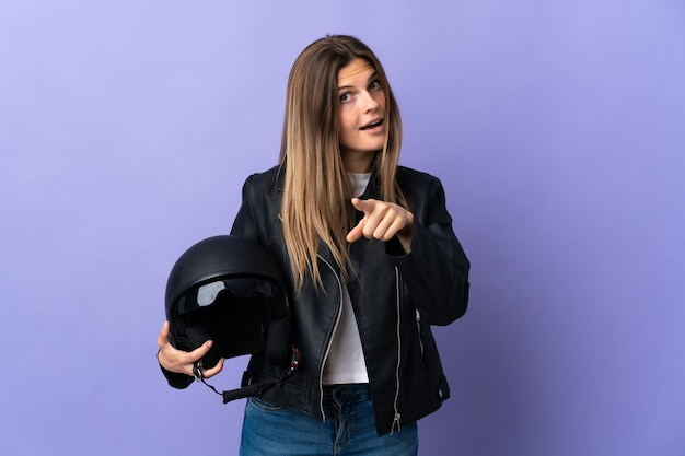 紫色の壁に分離されたオートバイのヘルメットを保持している若いスロバキアの女性は驚いて正面を指しています