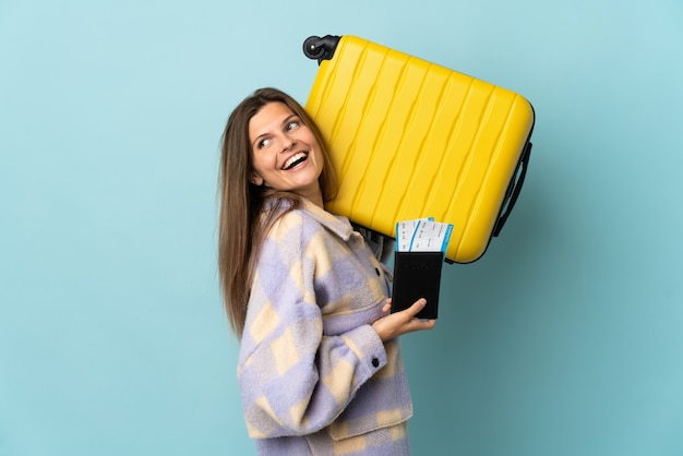 Young slovak woman isolated on blue wall in vacation with suitcase and passport