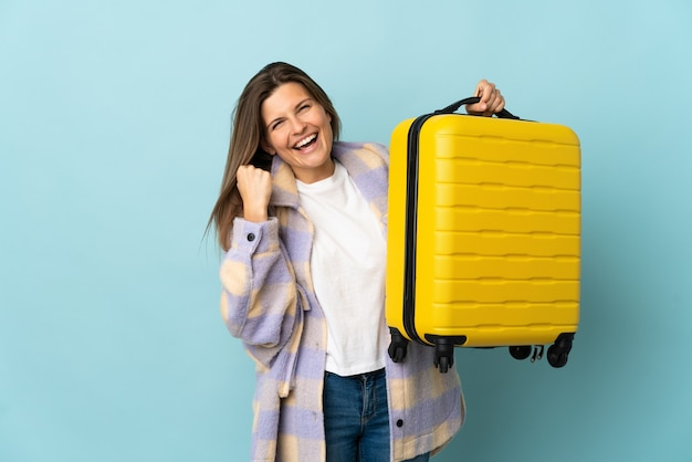 Young slovak woman isolated on blue wall in vacation with travel suitcase
