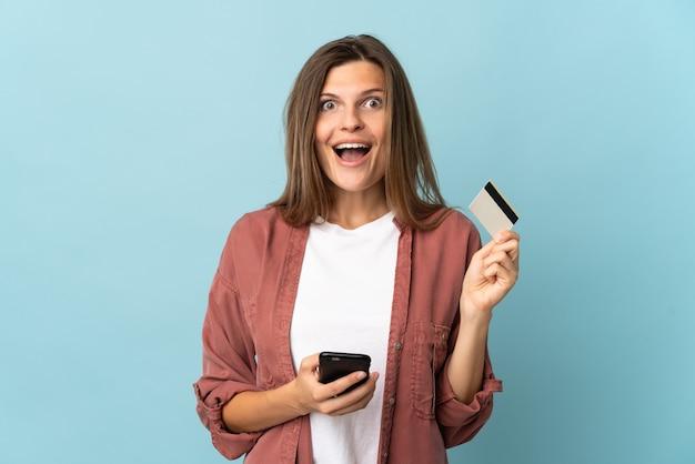 Молодая словацкая женщина изолирована на синем фоне, покупая с помощью мобильного телефона и держа кредитную карту с удивленным выражением лица