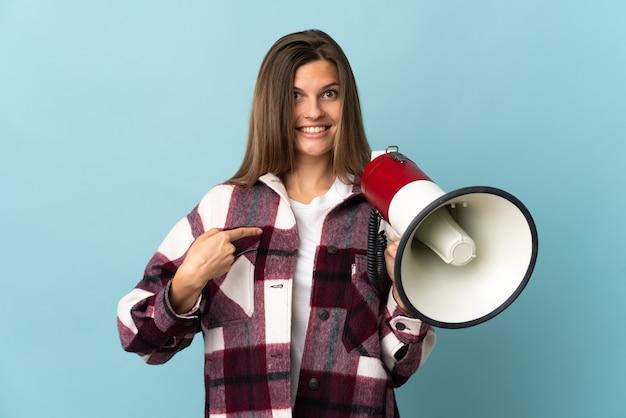 Молодая словацкая женщина изолирована на синем фоне с мегафоном и с удивленным выражением лица
