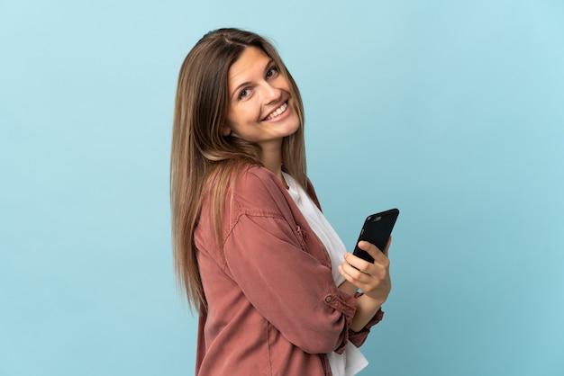 Молодая словацкая женщина изолирована на синем фоне с мобильным телефоном и скрещенными руками