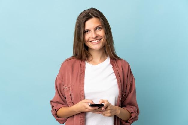Молодая словацкая женщина изолирована на синем фоне, глядя в камеру и улыбаясь при использовании мобильного телефона