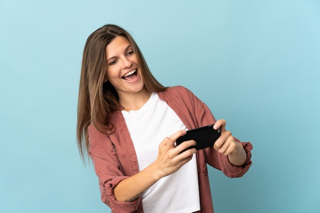 Молодая словацкая женщина изолирована на синем фоне, играя с мобильным телефоном