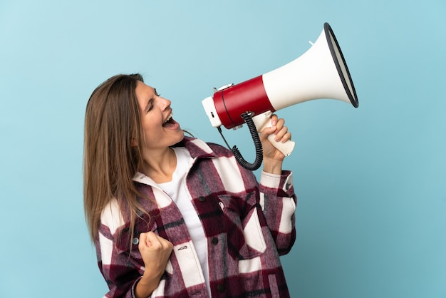 Молодая словацкая женщина, изолированная на синем фоне, кричит в мегафон, чтобы объявить что-то в боковом положении