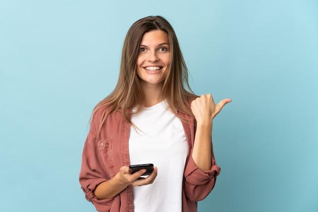 携帯電話を使用して、側面を指している青い背景で隔離の若いスロバキアの女性