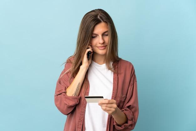Молодая словацкая женщина изолирована на синей стене, покупая с мобильного с помощью кредитной карты