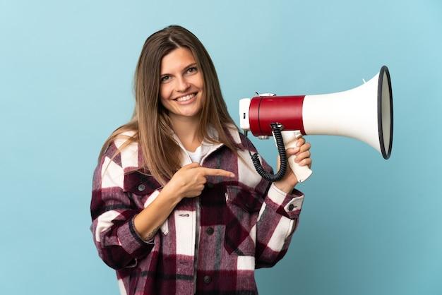 Молодая словацкая женщина изолирована на синей стене, держа мегафон и указывая сторону