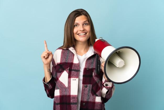 Молодая словацкая женщина изолирована на синей стене с мегафоном и показывает прекрасную идею