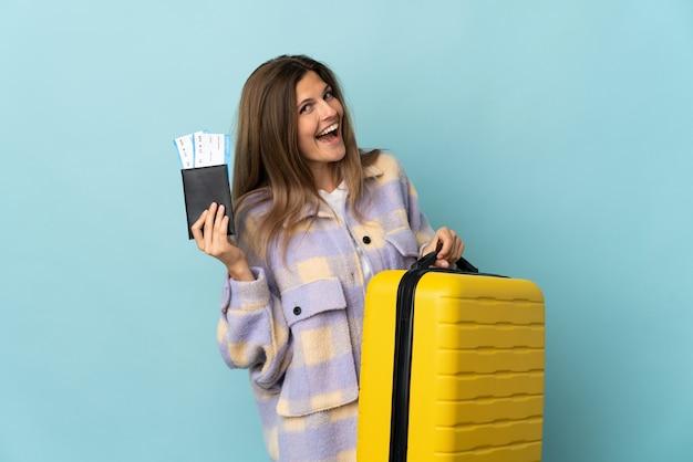 가방과 여권 휴가에 파란색 벽에 고립 된 젊은 슬로바키아어 여자