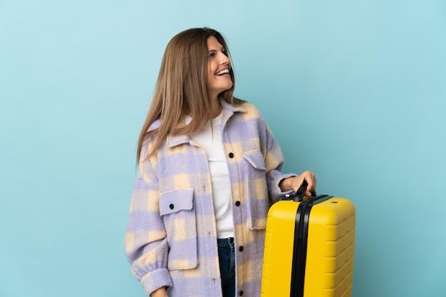 여행 가방으로 휴가에 파란색 벽에 고립 된 젊은 슬로바키아어 여자