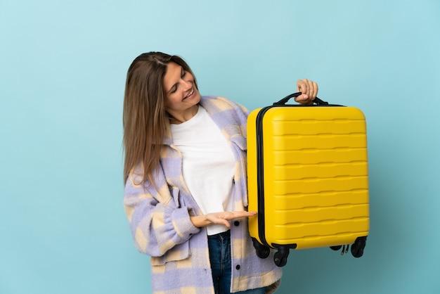 旅行スーツケースと休暇で青い壁に分離された若いスロバキアの女性