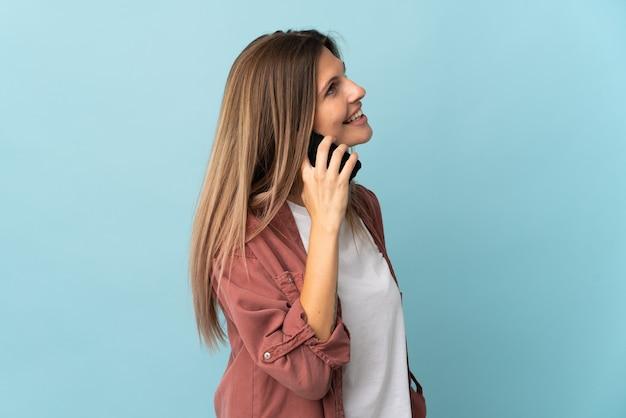 누군가와 휴대 전화로 대화를 유지하는 파란색 벽에 고립 된 젊은 슬로바키아어 여자