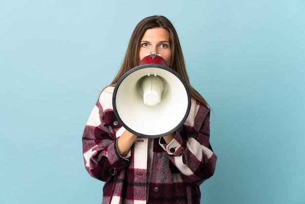 Молодая словацкая женщина изолирована на синей стене и кричит в мегафон, чтобы что-то объявить