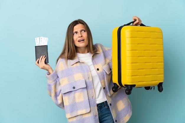 가방과 여권으로 휴가에 불행한 파란색 벽에 고립 된 젊은 슬로바키아어 여자