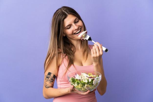 Молодая словацкая женщина изолирована на фиолетовом, держит миску салата и смотрит на нее со счастливым выражением лица