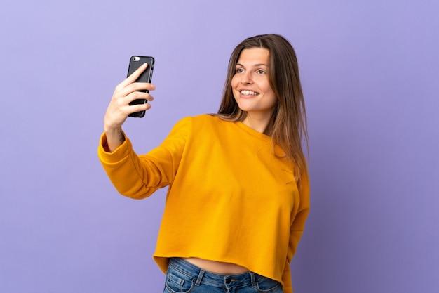 Молодая словацкая женщина изолирована на фиолетовой стене, делая селфи