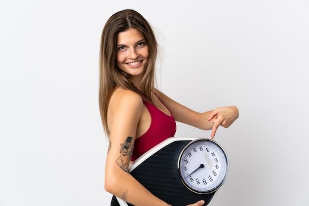 Молодая словацкая женщина изолирована на белом фоне, держа весы и указывая на него