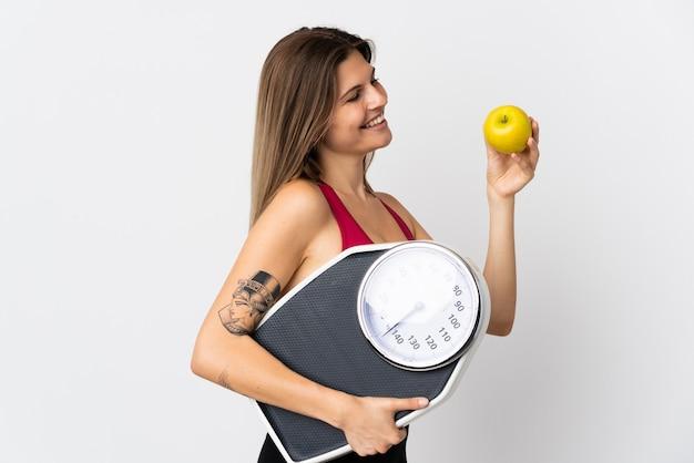 Молодая словацкая женщина, изолированные на белом фоне с весами и яблоком