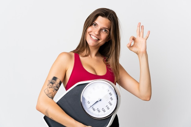 Молодая словацкая женщина, изолированная на белом, держит весы и делает знак ок