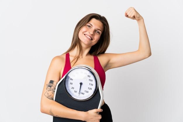 Молодая словацкая женщина, изолированная на белом, держит весы и делает сильный жест