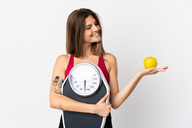 Молодая словацкая женщина, изолированная на белом, держит весы, глядя на яблоко