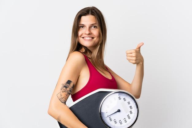 Молодая словацкая женщина изолирована на белой стене, держа весы с большим пальцем вверх