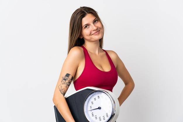 Молодая словацкая женщина изолирована на белой стене с руками на бедре и держит весы