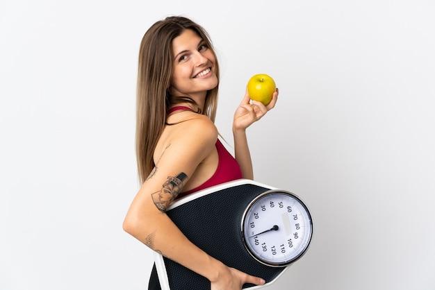 Молодая словацкая женщина изолирована на белой стене с весами и яблоком