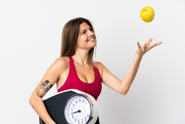 Молодая словацкая женщина, изолированная на белом, с весами и яблоком