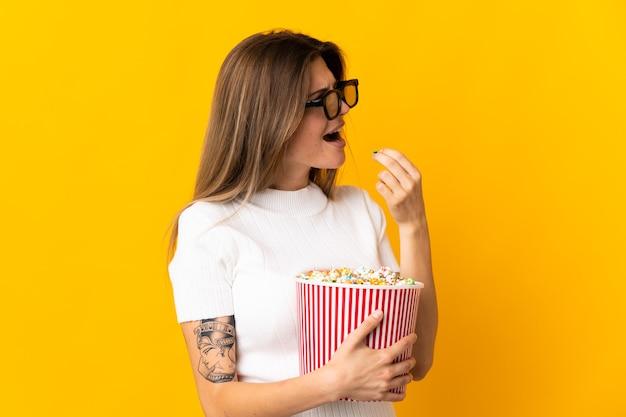 Молодая словацкая женщина изолирована на желтом в 3d-очках и держит большое ведро попкорна, глядя в сторону