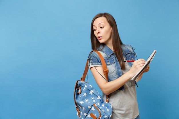 책가방을 들고 시험을 보는 데님 옷을 입은 교활한 호기심 많은 여학생이 파란 배경에 격리된 공책 연필을 들고 부정 행위를 합니다. 고등학교 대학 대학 개념의 교육입니다.