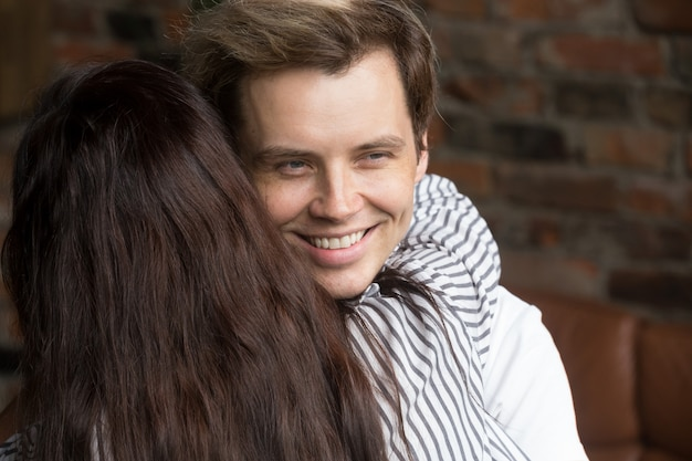Young sly liar man happily smiling while woman embracing him