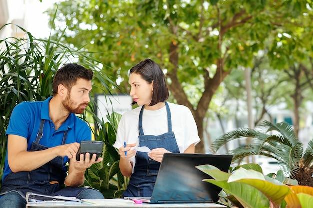 Молодые владельцы малого бизнеса обсуждают расходы и доходы в прошлом месяце, сидя за столиком в летнем кафе