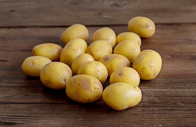茶色の木製のテーブルに若い小さなジャガイモ