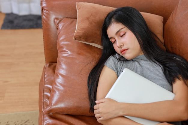 스마트하고 활동적인 젊고 활동적인 아시아 여성은 태블릿, 라이프스타일, 기술을 갖춘 거실에서 소파에 누워 잠을 자고 있습니다.