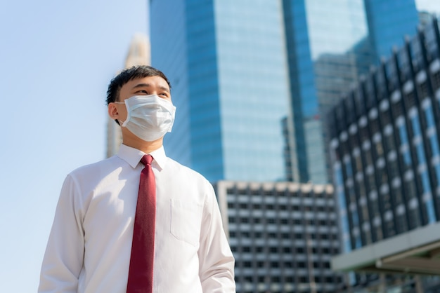 Young smart asian businessman in white shirt going to work in pollution city he wears protection mask prevent dust and covid-19